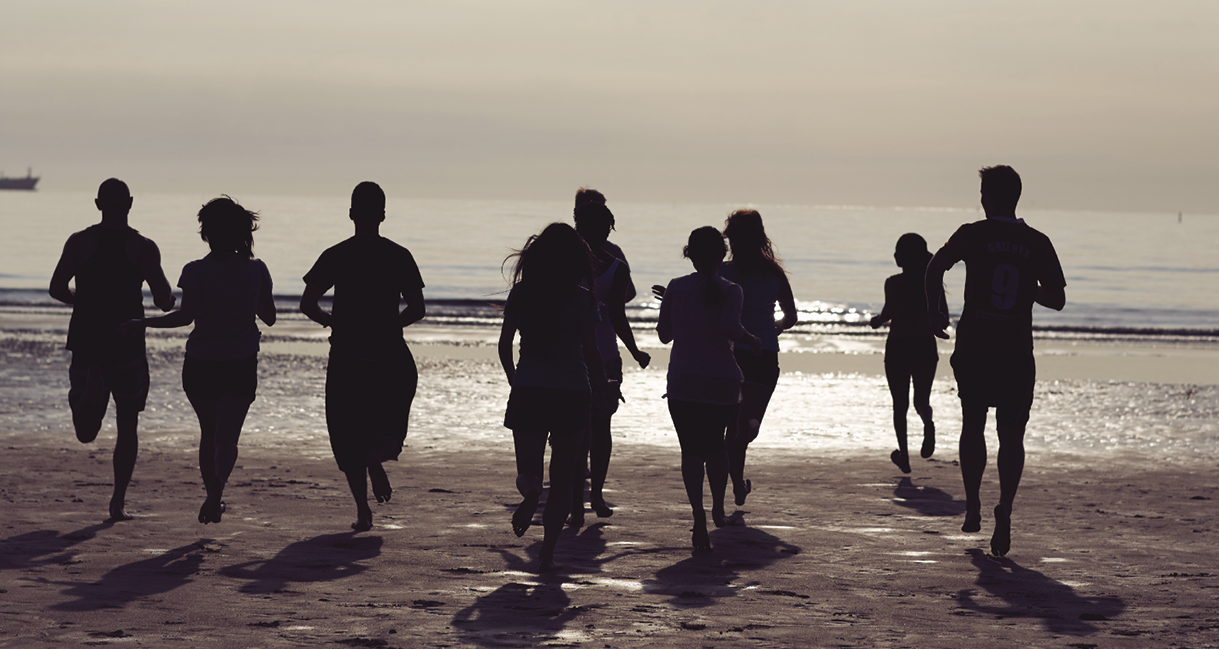 Image of students running on a beach