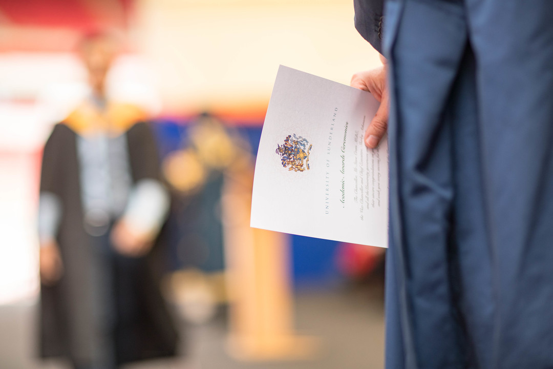 an image of a certificate being handed out at a graduation ceremony