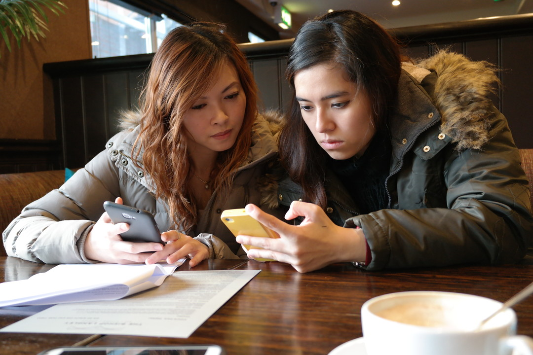 Two students on mobile phones