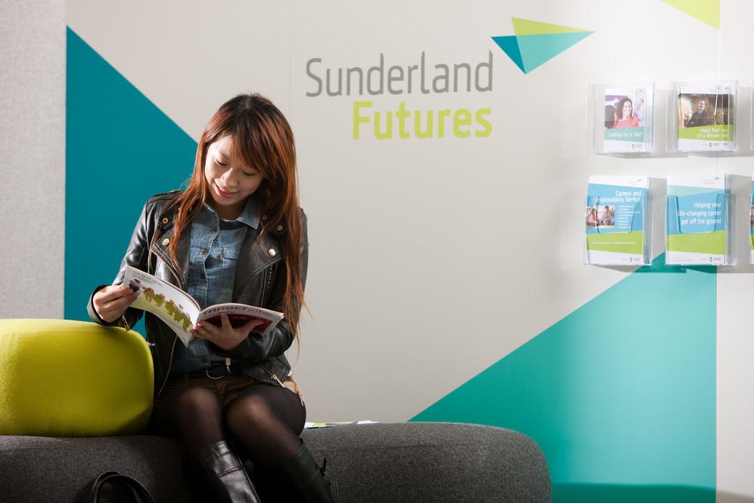 student reading a sunderland futures leaflet